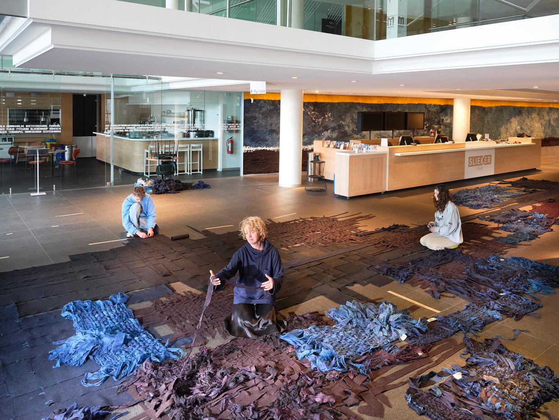 Kunstenaar Claudy Jongstra mag de entreehal van het vanwege de coronacrisis gesloten museum tijdelijk gebruiken als atelier. Ze werkt met haar team aan een stuk voor museum De Lakenhal in Leiden.