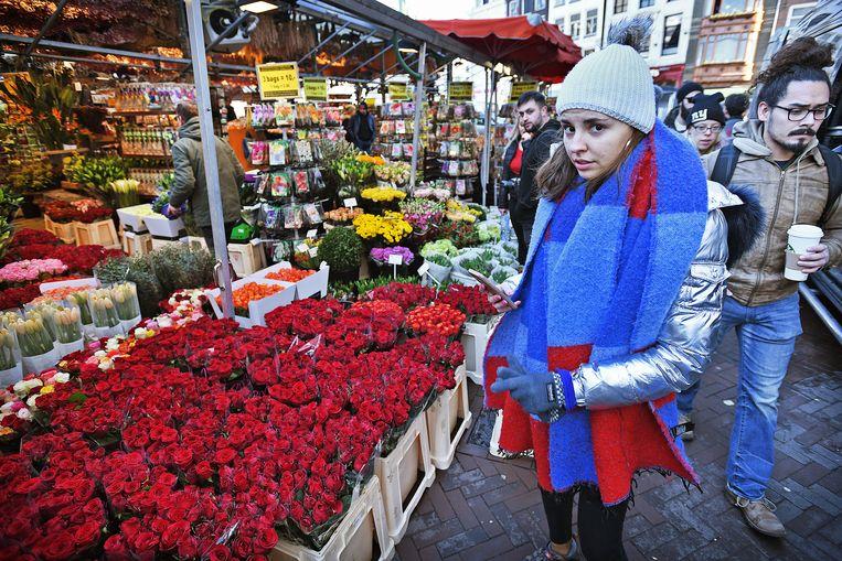 Een toerist op de bloemenmarkt in Amsterdam.  Beeld Guus Dubbelman / de Volkskrant