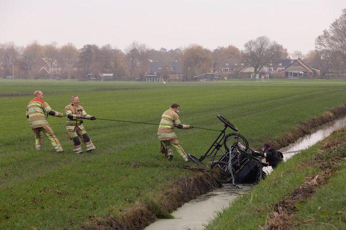 brandweerlieden trekken de wagen uit de sloot