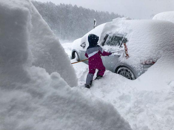 Een jongetje probeert een auto sneeuwvrij te maken in Salzburg.