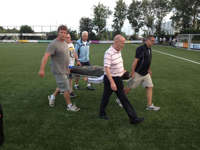 Tom Blomaard gaat na de zware overtreding van Alvin Daniels op een brancard het veld af.