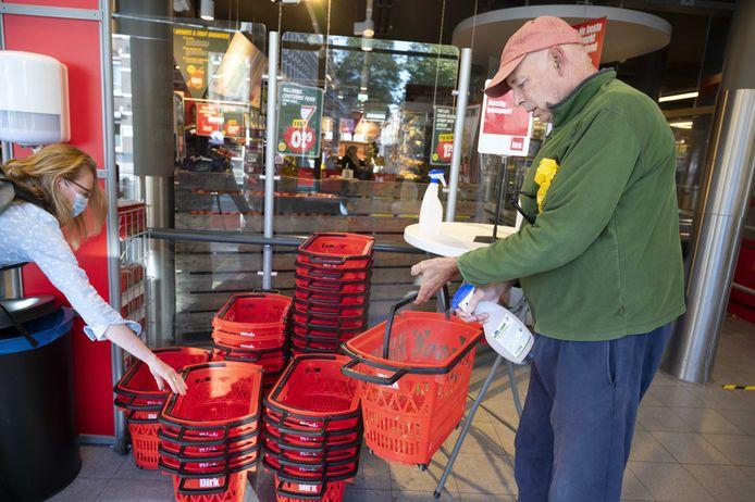 Een klant ontsmet een winkelmandje bij binnenkomst. Het is de bedoeling dat mensen vanaf nu ook een mondkapje gaan dragen in winkels.