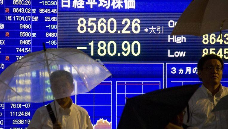 Japanners in de regen op straat voor een scherm dat de stand van de Nikkei-index weergeeft. Beeld epa