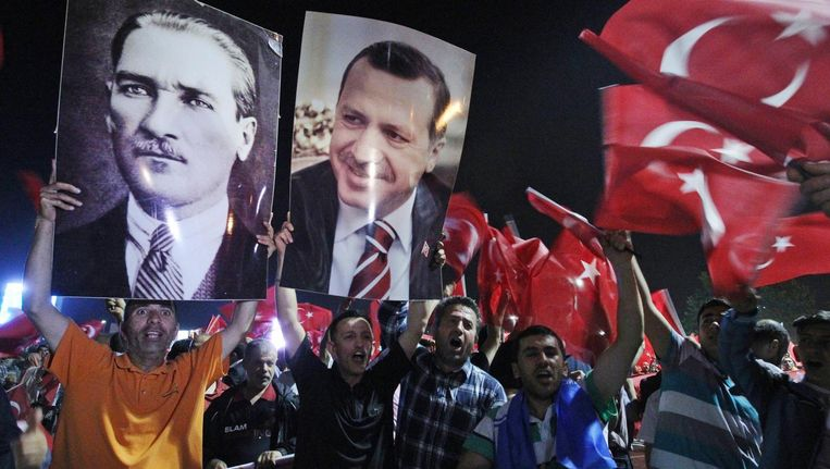 Supporters van de AKP houden de beeltenissen omhoog van Ataturk (links) en Erdogan (rechts). Beeld AP
