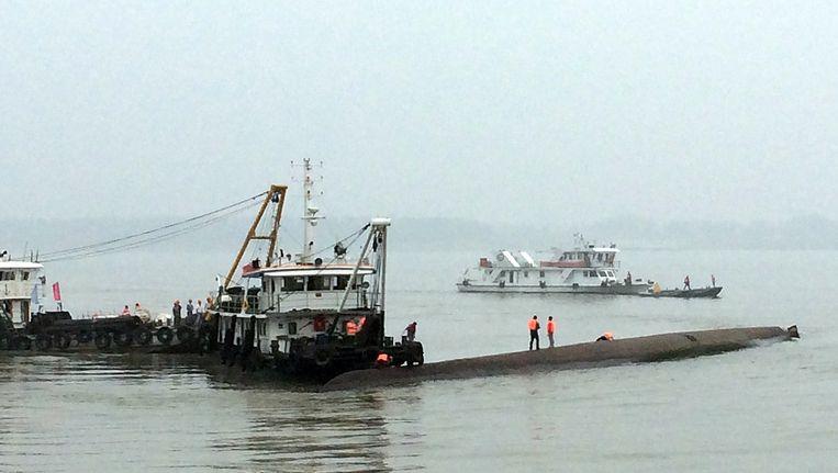 Chinese reddingsboten verzamelen zich rondom het gekapseisde passagiersschip. Beeld afp