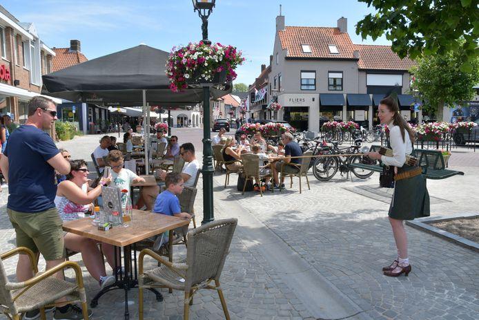 Lappie Lapstok legt, met humor, de 1,5 meterregel uit aan de terrasgangers in Sluis. De high five op afstand, bijvoorbeeld.
