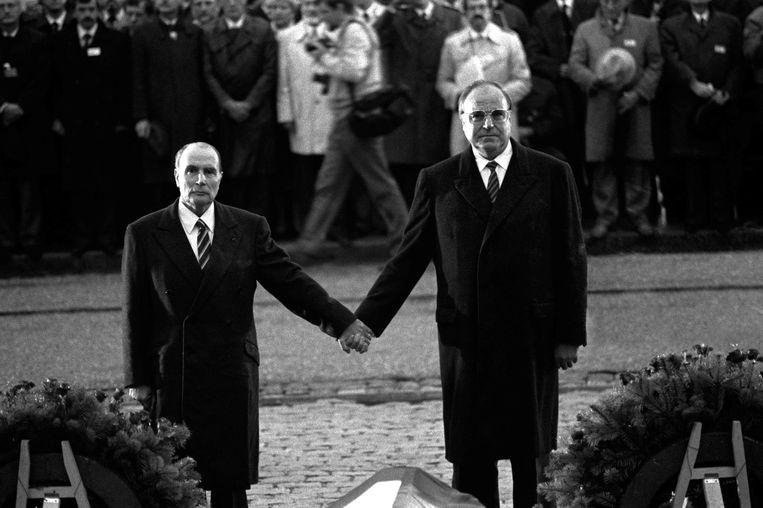 Helmut Kohl hand in hand met de Franse president François Mitterand bij een herdenking van oorlogsslachtoffers.  Beeld AFP