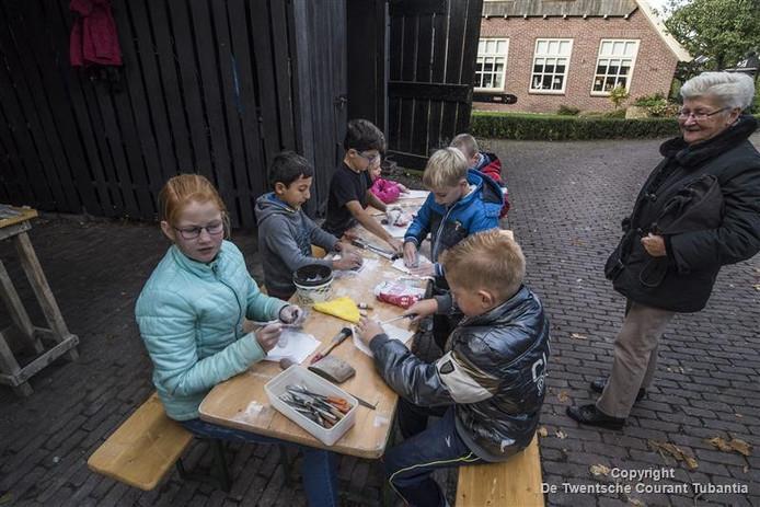 Kinderen volgen een workshop steen bewerken bij de Peddemorsboerderij.