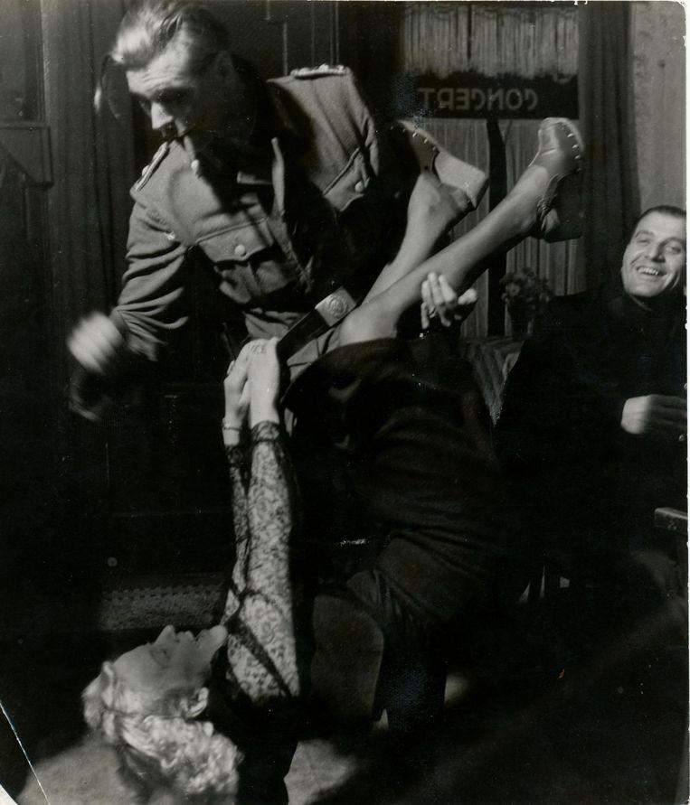 Een Duitse militair vermaakt zich met een Nederlandse vrouw. Beeld Foto: Kryn Taconis of Carel Blazer / NIOD