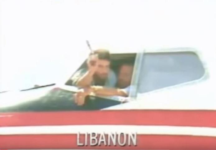 Een van de kapers laat zien dat hij een vuurwapen heeft waarmee hij de gezagvoerder onder schot houdt tijdens diens interview met de media op het vliegveld van Beirut.