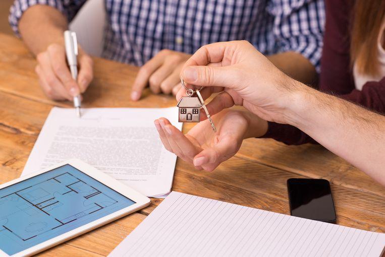 Een jong koppel ontvangt de sleutels van hun huis.