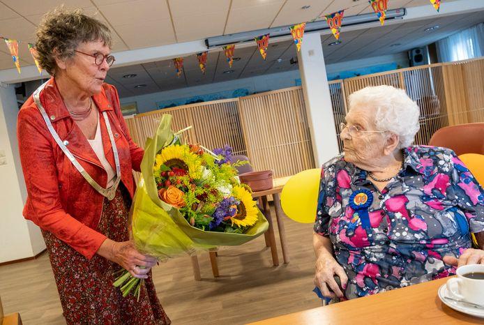 Loco-burgemeester Els Verhage (links) overhandigt mevrouw Van de Ven een boeket en felicitaties namens de gemeente Vlissingen.