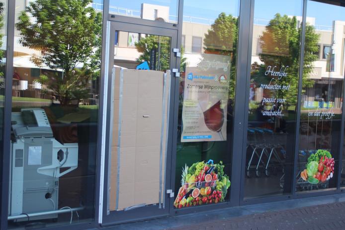 De haastig met karton dichtgemaakte deur bij de supermarkt. Inbrekers verschaften zich toegang door de ruit in te gooien.