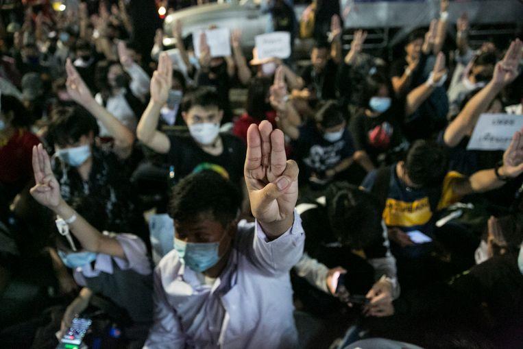 Demonstranten in Bangkok steken hun hand op met drie opgestoken vingers in teken van stil protest. Beeld Getty Images