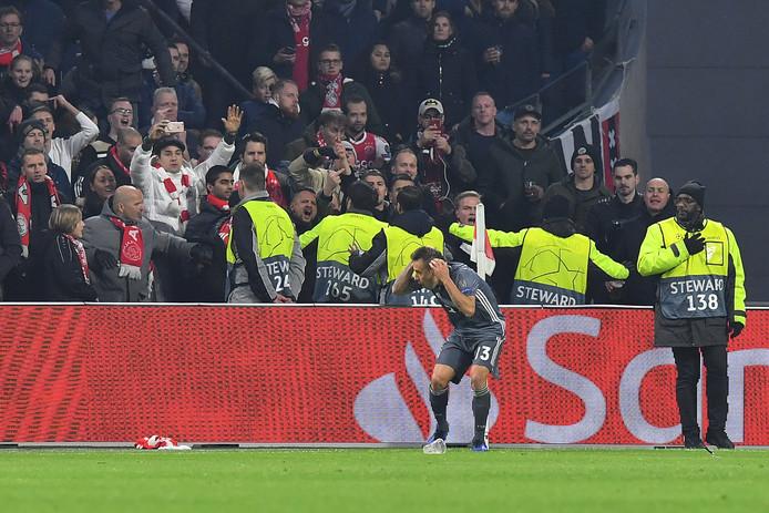 Stewards proberen te verhinderen dat fans van Ajax projectielen naar Bayern-verdediger Rafinha gooien.