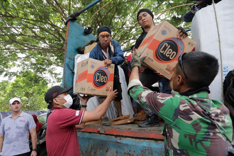 Vrijwilligers lossen hulpgoederen in Palu.
