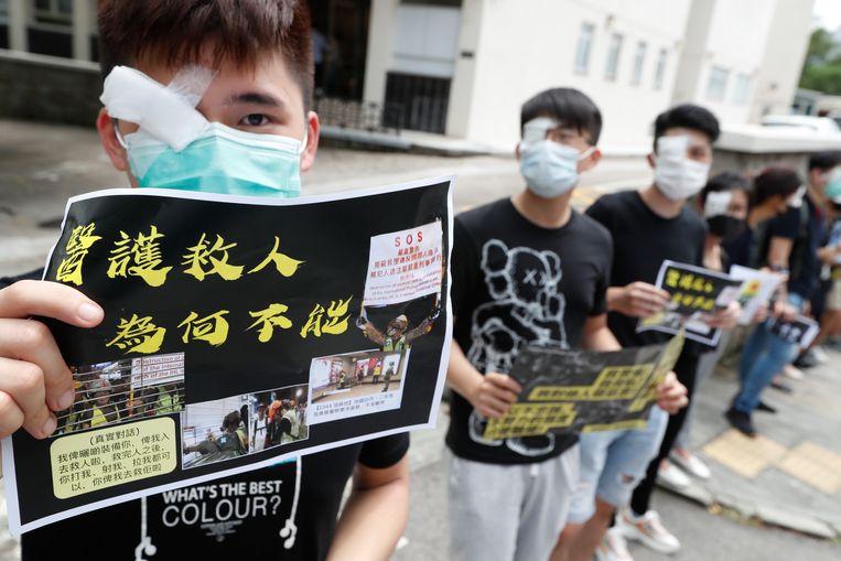 Studenten van de geneeskundefactulteit van de Universiteit van Hong Kong protesteren tegen politiegeweld tegen demonstranten, 5 september 2019. Hun rechteroog is bedekt uit solidariteit met een vrouw die gewond raakte tijdens botsingen met de politie. Beeld null