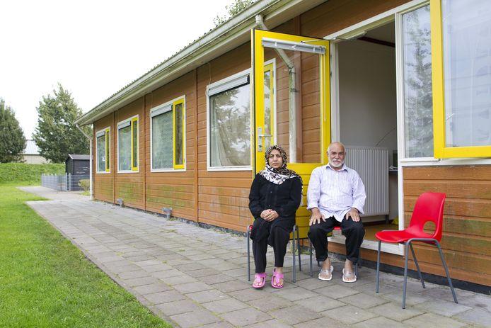 Een Afghaans echtpaar zit voor hun woning in het asielzoekerscentrum in Burgum.