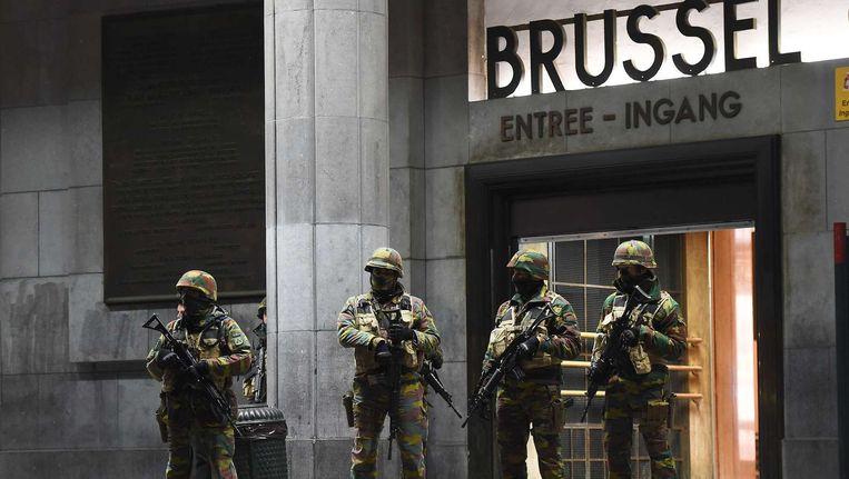Militairen zondag voor het station in Brussel. Beeld afp