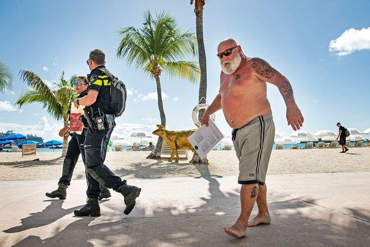 Een toerist verlaat het strand van Philipsburg terwijl twee Nederlandse agenten passeren. Beeld Guus Dubbelman / de Volkskrant