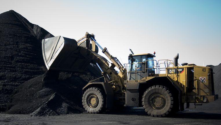 Een bulldozer verwerkt kolen in de haven van Amsterdam. Beeld ANP