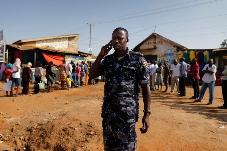 Een politieagent in Oeganda telefoneert.  Beeld EPA