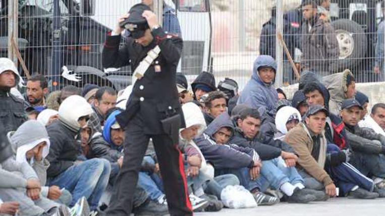 Een lid van de Italiaanse Carabinieri passeert vluchtelingen uit Tunesië, die wachten op overplaatsing naar een centrum waar hun asielaanvraag in behandeling kan worden genomen. (EPA) Beeld
