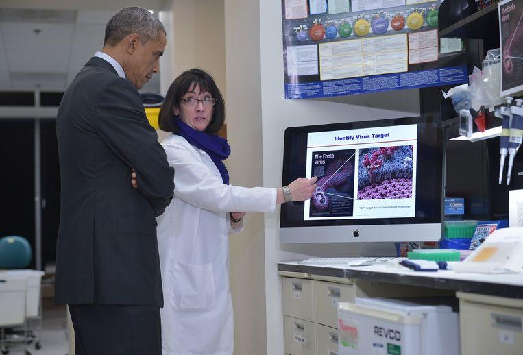 Een onderzoeker verstrekt uitleg over het ebolavirus aan Barack Obama. Beeld anp
