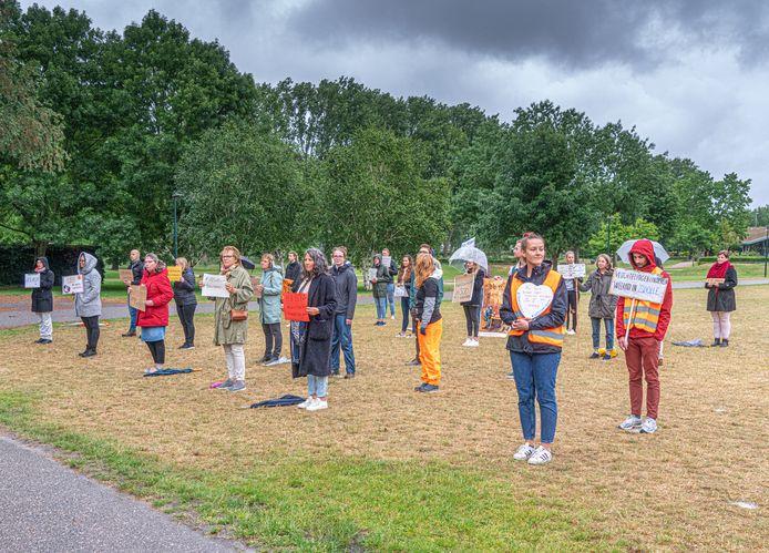 De circa dertig betogers in het Zwolse park Wezenlanden houden een indrukwekkend stil protest. Zij hoeven geen moeite te doen om onderling anderhalve meter afstand te bewaren.