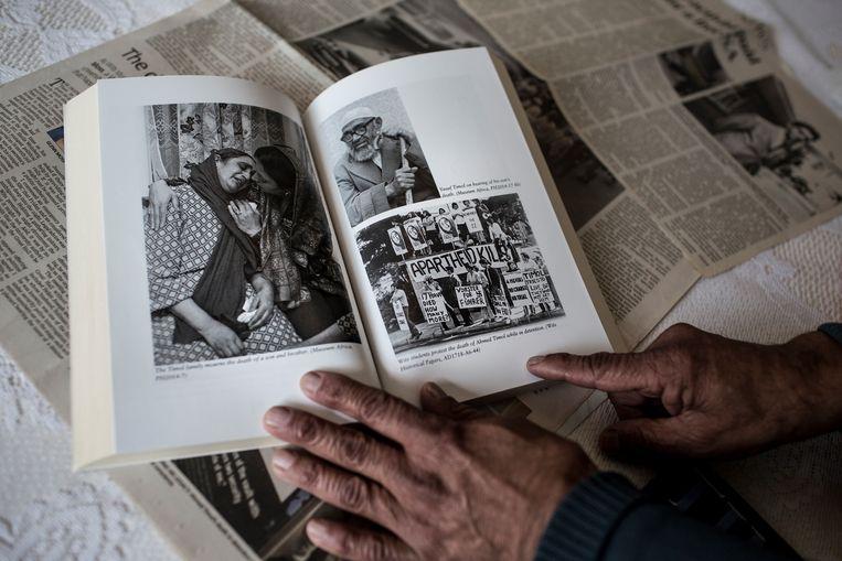 Voormalig anti-apartheidsactivist Mohamed Timol, broer van de vermoorde Ahmed Timol, toont een foto van het moment dat zijn ouders in 1971 horen dat Ahmed in politiehechtenis is omgekomen.  Beeld Hollandse Hoogte / AFP