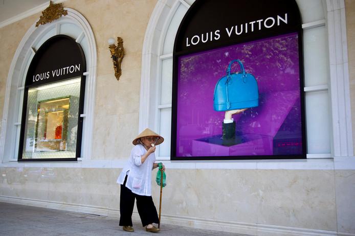 Een vrouw loopt langs een winkel van modehuis Louis Vuitton in Hanoi, Vietnam.
