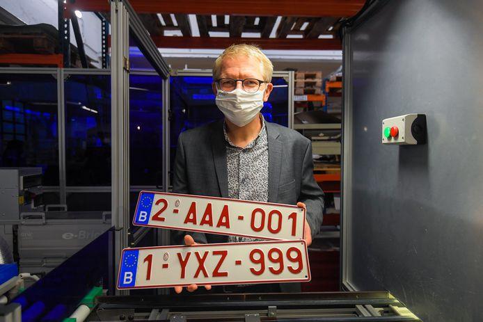 Minister van Mobiliteit Georges Gilkinet met de laatste nummerplaat die begint met indexcijfer '1' en de eerste die begint met '2'.