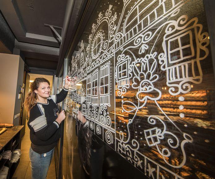 Anique Bossink bij haar raamkunstwerk bij bakkerij van Benthem in Oldenzaal.