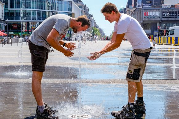 Arbeiders van nabijgelegen werf komen zich verfrissen aan de fontein op het De Brouckèreplein.