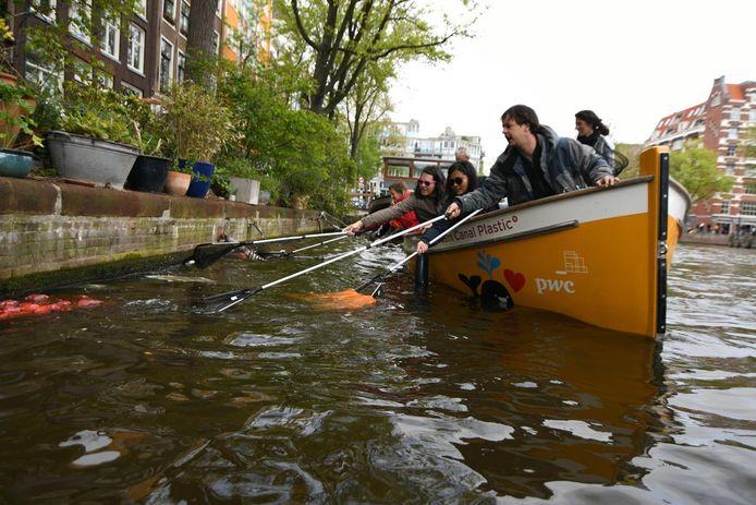 Amsterdammers vissen plastic uit de grachten na Koningsdag.