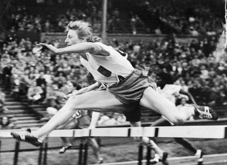 Fanny Blankers-Koen in actie.  Ondanks alle aandacht bleef atletiekkampioen Fanny Blankers-Koen volgens de schrijvers van haar biografie gewoon: 'De benen, die sterk genoeg waren om Fanny Blankers-Koen in 11,2 seconde over tachtig meter sintelbaan en acht horden van 76,2 cm hoogte te dragen, zijn heus ook sterk genoeg om die 'weelde' te dragen.' (1949) Beeld AFP