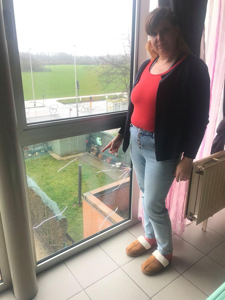 Ann Verswijvel toont in haar appartement hoe de ruiten gebarsten zijn.