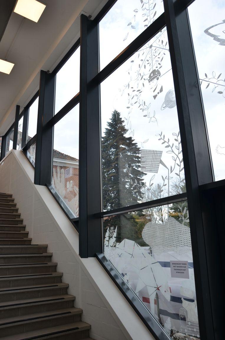 De nieuwe glazen wand aan de trappenhal vormt een levensgroot canvas voor de raamtekeningen van Joke Dieleman en Isa De Wispelaere.