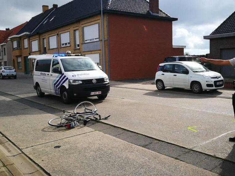 De witte auto schepte de fietser op. Zes omstaanders tilden de auto op om de fietser van onder de wagen te halen.