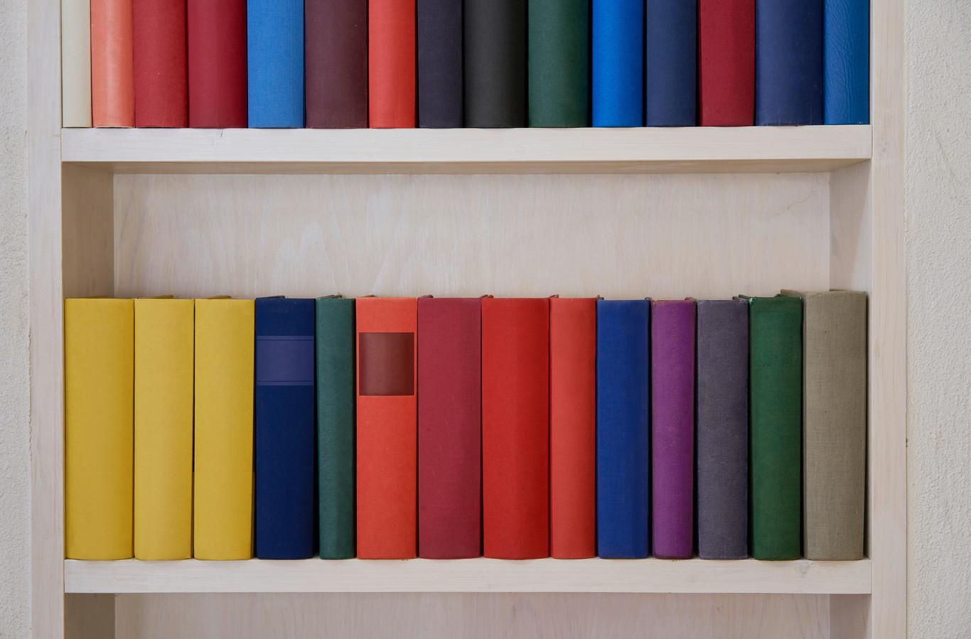 De boeken met nieuwe kaft gesorteerd op kleur.