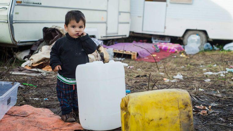 Een kindmigrant met watercontainers in de jungle van Calais. Beeld EPA