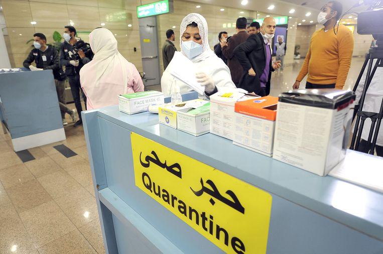 Medewerkers van de Egyptische Quarantaine-authoriteit meten de lichaamstemperatuur van pas aangekomen reizigers op de internationale luchthaven van Caïro om mogelijke gevallen van het coronavirus op te sporen.