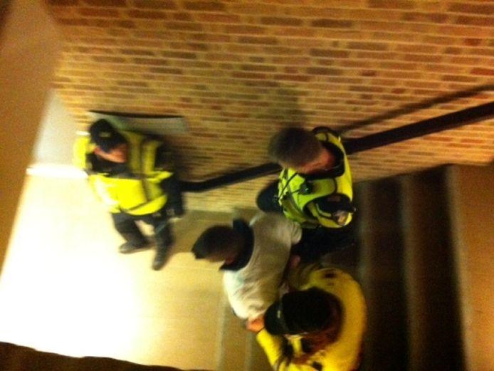 Een arrestant wordt in het raadhuis afgevoerd door de politie.