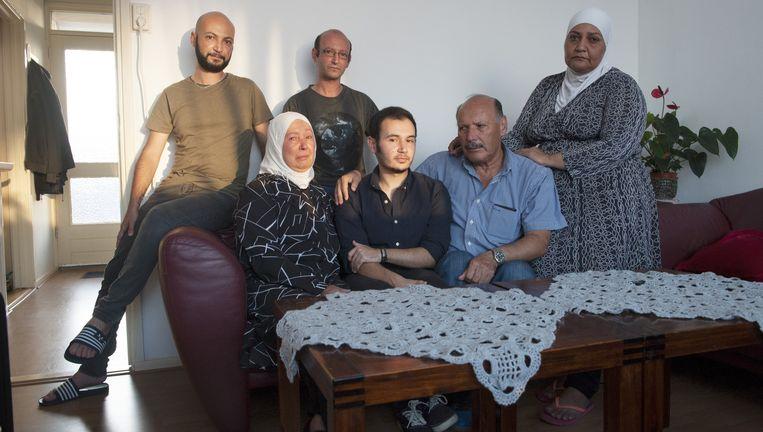 De familie Deeb in hun huis in Vlaardingen. Op de bank Houmam tussen zijn moeder Fawziyeh en vader Raja. Achter hem, van links af, zijn broers Adham en Hasan en tante Fouda. Beeld An-Sofie Kesteleyn / de Volkskrant
