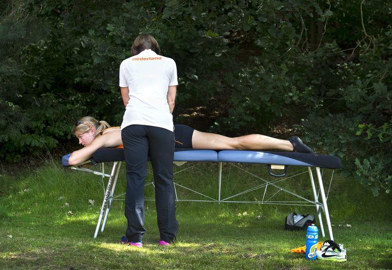 Dafne Schippers traint op Papendal met coaches Bart Bennema (zonnebril), Rana Reider en fysiotherapeut. Beeld null