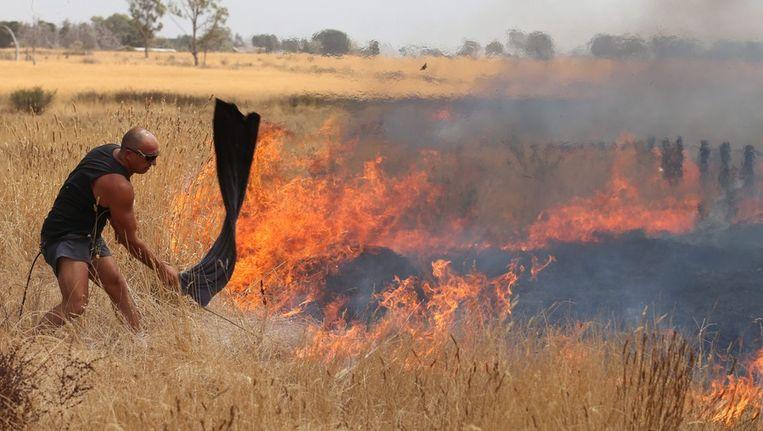 Een inwoner van Craigieburn, een voorstad van Melbourne, probeert zondag de vlammen onder controle te krijgen. Beeld epa