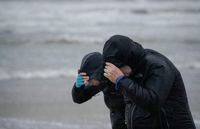 Wandelaars trotseren de storm op het strand van Egmond aan Zee.