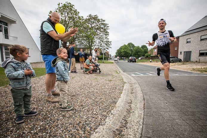 Dirk groet zijn zoontjes terwijl hij een marathon loopt in zijn eigen wijk.