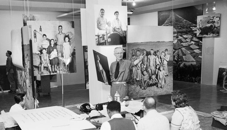 Fotograaf en toenmalig MoMA-directeur Edward Steichen (staand in het midden) arrangeert foto's voor de tentoonstelling 'Family of Man' (1955), met 500 foto's van meer dan 280 fotografen uit 68 landen. Beeld Bettmannarchief