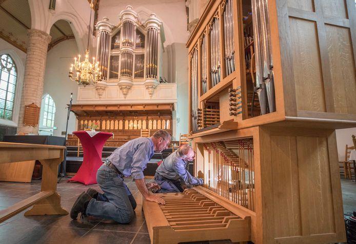 Orgelbouwer René Nijsse (links) werkt samen met Sjaak Moerenhout aan de balg van het nieuwe kerkorgel. Op de achtergrond is het grote orgel van de Nederlands hervormde kerk in Kapelle te zien.